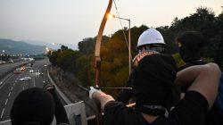 Demonstran mengarahkan panah ke jalanan untuk menghalau kendaraan di luar Universitas China Hong Kong (Foto: AFP)